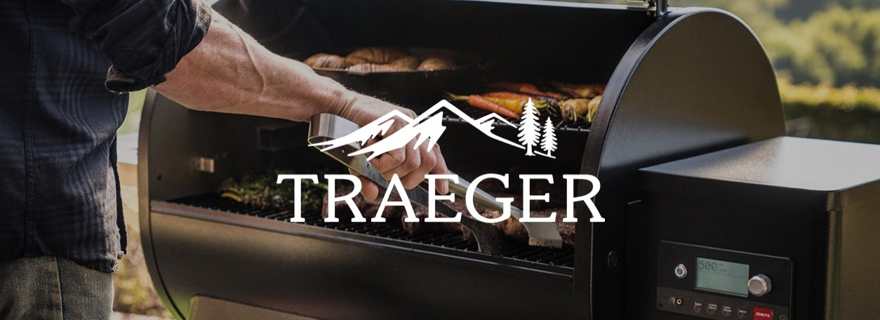 Man grilling on Traeger grill with logo